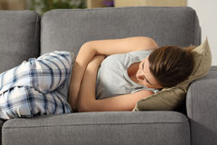 Teen suffering belly pms symptoms. Lying on a sofa in the living room at home Stock Photos