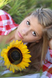 Teen with sunflowers. Beautiful teen girl in a field with sunflowers royalty free stock image