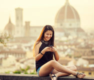 Teen at sunset in Florence uses the smartphone Stock Images