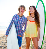 Teen surfer couple on beach shore with surf boards. High key Royalty Free Stock Image
