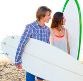 Teen surfer couple on beach shore with surfboards. High key Stock Photography