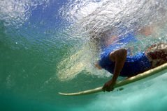 Teen Surfer Duckdiving. A teen shortboard surfer duckdiving a beautiful wave in hawaii stock photo
