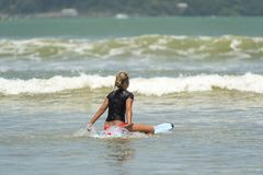 Teen surfer on the water. Teen surfer on her board at sea waiting for a good wave in Weligama, Sri Lanka. Weligama is a perfect spot in Sri Lanka for beginner Royalty Free Stock Photo