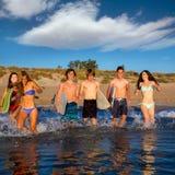 Teen surfers group running beach splashing. Teen surfers boys and girls group running happy to the beach splashing water Royalty Free Stock Photography