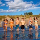 Teen surfers group running beach splashing. Teen surfers boys and girls group running happy to the beach splashing water Stock Image