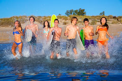 Teen surfers group running beach splashing Royalty Free Stock Photo
