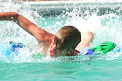 Teen swimming. Teen boy racing in the swimming pool Royalty Free Stock Photo