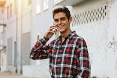 Teen talking on cell phone. Smiling teen talking on cell phone in urban alleyway on sunny day Royalty Free Stock Photo