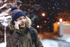 Teen talking on the phone on a city street in winter. Happy young man talking on the phone on a city street in winter Royalty Free Stock Photos