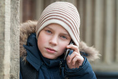 Teen talking on the phone. Urban teenager standing at the wall of the building and talking on the phone Stock Photos