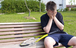 Teen tennis player. Depressed teenage boy sitting on a bench with tennis racket Royalty Free Stock Photos