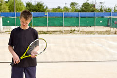 Teen tennis player lost. Teenage tennis player boy sad after a lost match Stock Photo