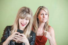 Teen Texting. Upset women with laughing teen on cell phone Royalty Free Stock Photos