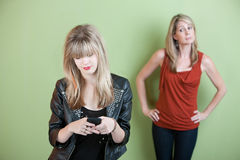 Teen Texting. Concerned mom watches teen send text messages on phone Royalty Free Stock Photo