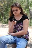 Teen texting on cell phone. A multicultural (Asian and Caucasian) 13-year-old young teen girl reads a text message on her cell phone and has a serious expression Royalty Free Stock Photography
