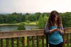 Teen texting. Teen girl texts at a park Royalty Free Stock Photos