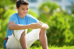 Teen texting in the park. Image of a young Hispanic teenager texting in a park setting Stock Photography