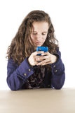Teen texting. A teenage girl texting on her phone sitting at a table Stock Photos