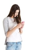 Teen texting to someone. Brunette teen texting to someone Royalty Free Stock Photo