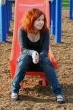 Teen Thinking On Sliding Board. Teen girl sitting on the end of a playground sliding board thinking stock images