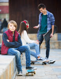 Teen took offence at friends. Envy male teen sitting aside of girlfriend talking with boy outdoors Stock Image