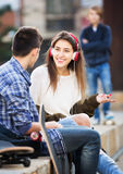 Teen took offence at friends. Envy male teen standing aside of girlfriend talking with boy Royalty Free Stock Image