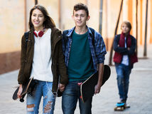 Teen took offence at friends. Portrait of upset male teen standing aside of girlfriend talking with boy Stock Photos