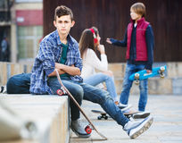 Teen took offence at friends. Upset male teen sitting aside of girlfriend talking with boy Stock Image