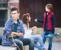 Teen took offence at friends. Upset male teen sitting aside of girlfriend talking with boy in the city Royalty Free Stock Image
