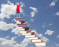 Teen on top of book staircase Royalty Free Stock Photos