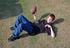 Teen Touch Football. A teenaged boy lies on the ground with a football in his hand in the midst of a touch football game Royalty Free Stock Images