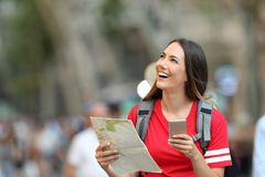 Teen tourist holding guide and phone looking above royalty free stock image