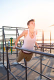 Teen training on parallel bars outdoors Royalty Free Stock Images