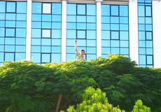 Teen on tree. At office building Stock Image