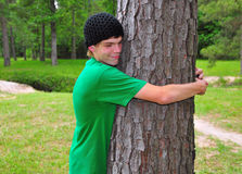 Teen Tree Hugger. A teen in a green tee shirt hugs a tree in the forest Royalty Free Stock Photography