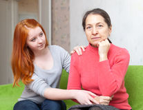 Teen tries reconcile with her mother. In home. Focus on mature woman Royalty Free Stock Image