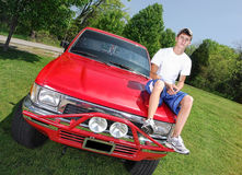 Teen on Truck Hood. A teenage boy looking tough sitting on a truck hood Stock Photography