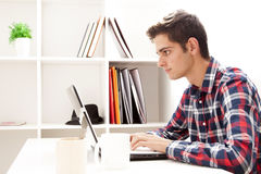 Teen typing on computer. Teen boy typing on laptop computer inside home Royalty Free Stock Photos