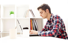 Teen typing on home laptop. Teen boy typing on laptop computer inside home office Stock Photo