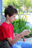Teen typing a text message. Teen is sitting and messaging from his mobile phone outdoors Stock Image