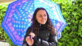 Teen with umbrella in a garden stock footage