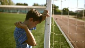 Teen upset defeat boy by knocking goal goal post. Teen upset  defeat boy by knocking goal goal post net stadium turf stock video footage