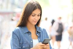 Teen uses a smart phone in the street. Teenager uses a smart phone standing in the street Stock Photography