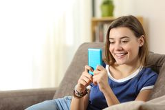 Teen using a blue smartphone at home. Happy teen using a blue smartphone sitting on a couch in the living room at home Royalty Free Stock Photo