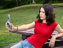 Teen using camera phone. Teenage girl using camera feature of cell phone Stock Photography