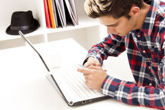 Teen using cellphone and laptop. Teen boy using cellphone and laptop computer sitting at home office desk Royalty Free Stock Photo