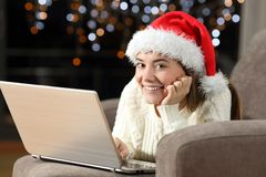 Teen using a laptop and looking at you in christmas royalty free stock photography