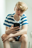 Teen using smartphone on toilet. Front view of boy teenager sitting on toilet seat pantless looking at smartphone in his hand Royalty Free Stock Images