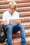 Teen using tablet computer. Teen boy using tablet computer outdoors Royalty Free Stock Photography