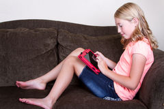 Teen using tablet. While sitting or relaxing on couch stock image